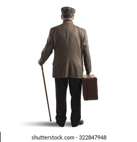 Old man back with suitcase and stick