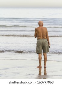 Old man with bathing suit on the beach