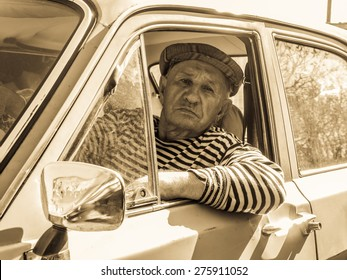 the old man behind the wheel of an old car. Retro stylized photo.