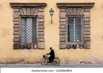 An old man in bike in front of an ancient palace