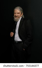 Old man in black suit and white shirt standing against black background. Stylish elderly male with long grey hair and beard.