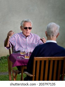 Old man with black sunglasses explaining something to another old man