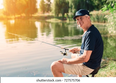 An old man in a black T-shirt and a black cap sits on the riverbank at dawn and catches fish for spinning. He looks at the camera, against the background of the water with a reflection of the forest