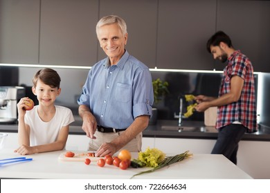 An old man in a blue shirt posing in the kitchen with his grandson preparing a salad for Thanksgiving. Behind them the boy's father washes salad leaves