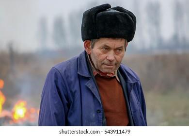 Old man burning the garbage at winter