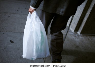 An old man carrying a plastic bag