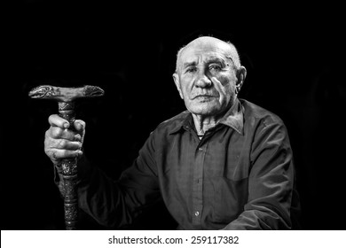 old man with a carved wooden cane
