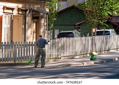 An old man is cleaning up the street in Tallinn, Estonia. He was there at work every single morning.