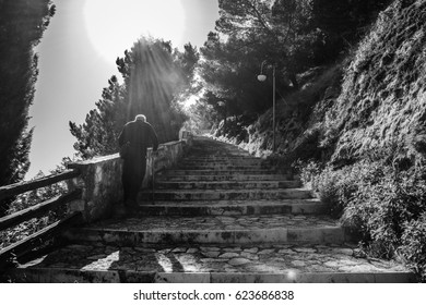 OLD MAN CLIMBING THE STAIRS OF A MONASTERE