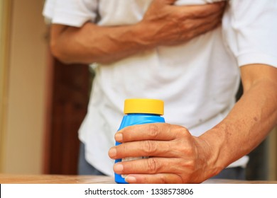 Old Man clutching his chest from acute pain and pick up his medication.Sublingual pill for relieve symptom of heart attack.Emergency condition.Healthcare and medical concept.