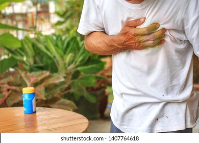 Old Man clutching his chest from acute pain.Heart attack from myocardial infarction.Emergency condition.Sublingual pills for relieve pain on the table.Healthcare and medical concept.