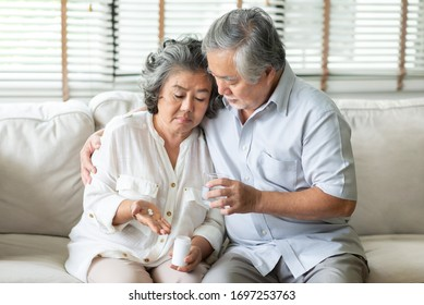Old man comforting his wife while her having a cold. Elderly woman holding pills or medicine on her hand while having fever at home. Illness, Disease, Coronavirus, virus, Covid-19, Quarantine.