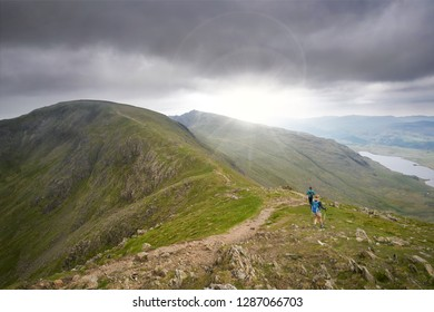 OLD MAN OF CONISTON, ENGLAND, UK - MAY 04, 2016: Two hikers walking along Swirl Band towards the summit of the Old Man of Coniston in the English Lake District.