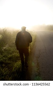 An old man with crutches walking along the road, sunrise and mist