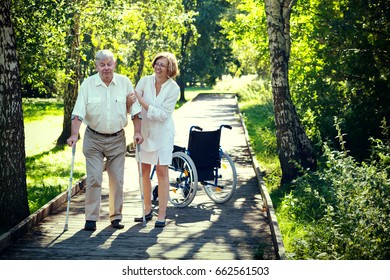 old man with crutches and young female medical assistant in the park