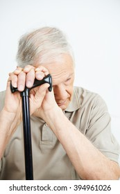 Old man with depression putting his hands on a cane