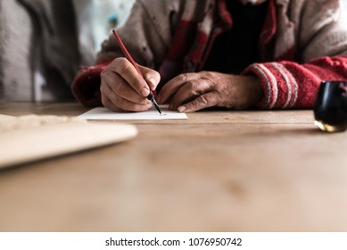 Old man with dirty hands writing a letter using a nib pen and ink or pigment from a pot in a low angle view across a wooden table.
