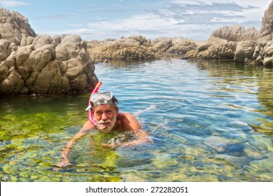 Old man doing snorkelling. Shot on the Otter trail in the Tsitsikamma National Park, Garden Route area, Western Cape, South Africa.