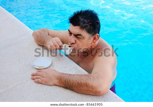 old man drinking coffee in a pool