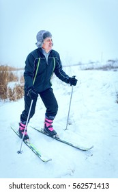 An old man exercises to improve his health by cross country skiing.