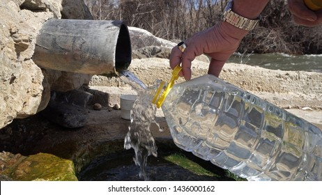 Old man fill plastic bottle with thermal drink water from natural spring