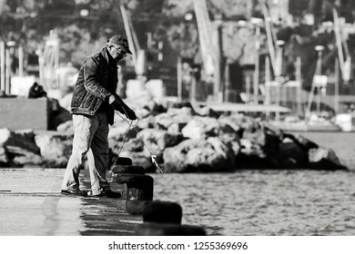 An old man fishing with a rope from the pier of a port in Salerno. Italy-Salerno 05 December 2018