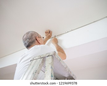Old man fixing drywall suspended ceiling to using screwdriver, Renovate house do it yourself concept.