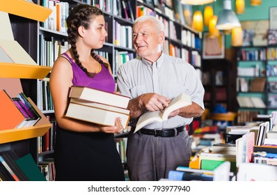 Old man and girl discuss a book in a bookstore