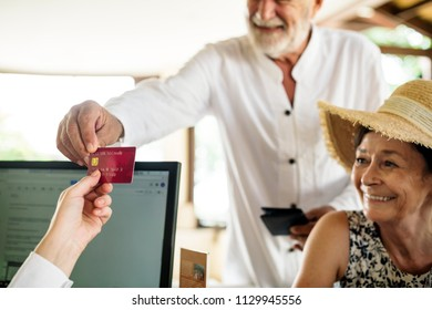 Old man giving credit card to receptionist