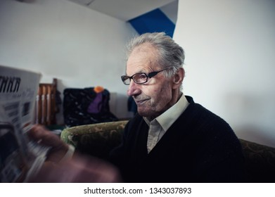 Old man with glasses having problems reading the newspapers