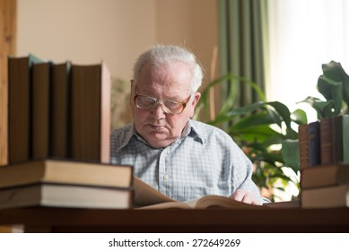 Old man in glasses reading a books in the room. Close portrait