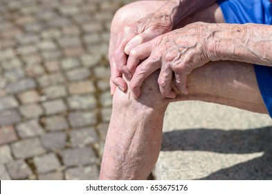 Old man with gnarled hands with pronounced veins clutching his knee as he sits outdoors on a stone bench in a close up view of the ageing process