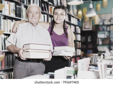Old man with granddaughter are showing their purchases in bookstore