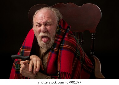 Old man with gray beard with bright red plaid shawl sits hunched over his cane and sticks out his tongue. Head and shoulders portrait in a low key horizontal image.