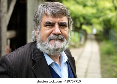 old man with gray hair and beard outside next to an alley