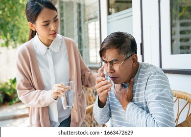 Old man with gray hair choke and cough, so private nurse give him the glass of water.