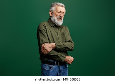 old man in green T-shirt and jeans with closed eyes holding his elbow in pain in the studio with green wall, help me, I've broken my arm