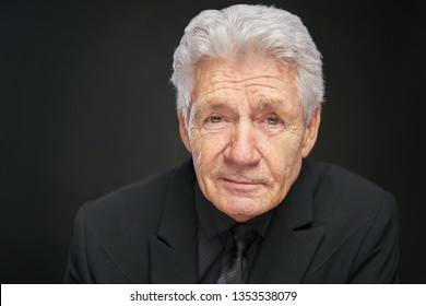 Old Man with grey har and black suit on black studio background