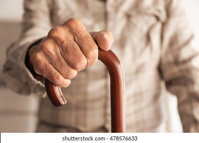 Old man hand holding walking stick
