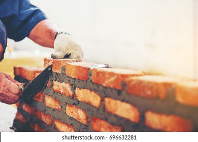 Old man Hand white-wash cement built wall brick new house, Bricklayer worker installing brick masonry on exterior wall with trowel putty knife  local county in Thailand