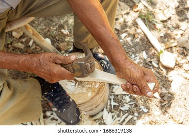 Old man handcrafting a wood sppon the traditional way of making tools in the villages of Romania and Eastern Europe
