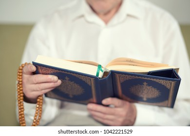 An old man hands holding the Koran