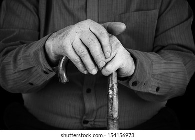 Old man hand's on wood cane in black and white