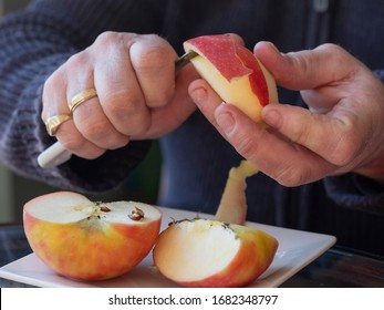 Old man hands peeling organic red Pink Lady apple outside over a bowl of apple slices