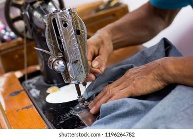 Old man hands working with old sewing machine.