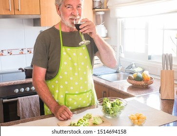 The old man has finished cutting the broccoli and enjoying a glass of red wine. One elderly people gray hair