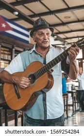 Ein alter Mann mit Hut, der in einer Bar in Havanna, Kuba, eine akustische Gitarre spielt.