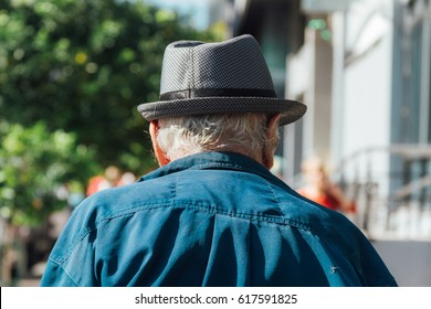 Old man with hat seen from behind walking down the street
