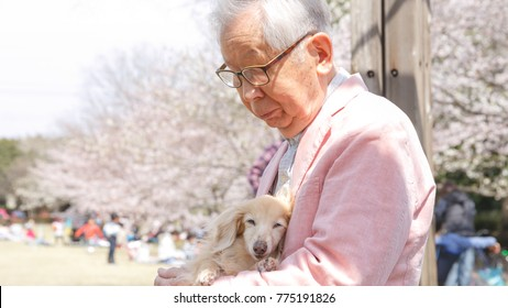 An old man holding a dog
