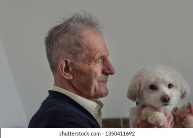 Old man holding a maltese dog